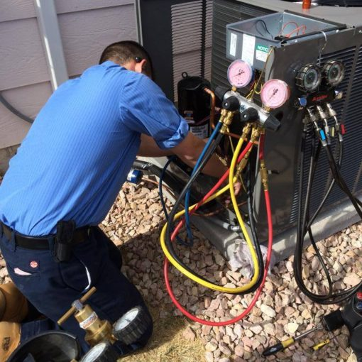 Service technician working on an Air Conditioning Condenser - air conditioner is not working properly
